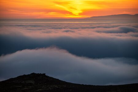 Dreamy misty landscape above the sea of clouds, mountains at sunset in Iceland Zdjęcie Seryjne