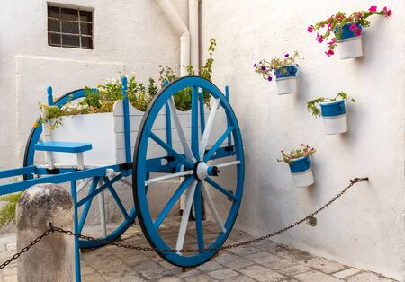 A wooden car painted white and blue decorated with flowers in Polignano a Mare. Apulia, Italy