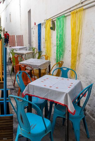 Colorful arrangement of the cafe in one of the side streets of Polignano a Mare. Italy Zdjęcie Seryjne