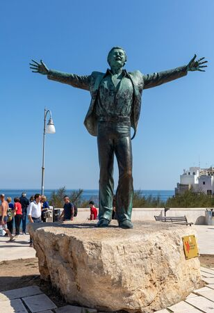 Polignano a Mare, Italy - Sept 17, 2019: Statue of the Italian singer and songwriter Domenico Modugno famous for the song Volare was born in Polignano a Mare. Italy. The author of the sculpture is Herman Mejer Publikacyjne