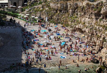 Polignano a Mare, Italy - September 17, 2019: People relax and swimming on lovely beach Lama Monachile in Polignano a Mare, Adriatic Sea, Apulia, Bari province, Italy,