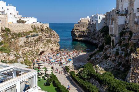 Polignano, Italy - September 17, 2019: People relax and swimming on lovely beach Lama Monachile in Polignano a Mare, Adriatic Sea, Apulia, Bari province, Italy,