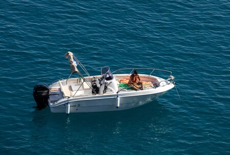 Polignano a Mare, Italy - September 17, 2019: A woman aboard a white speedboat against the blue Adriatic Sea in Polignano a Mare. Italy