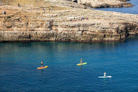 Polignano a Mare, Italy - September 17, 2019: People are swimming along the cliff in Polignano a Mare.  Apulia, Bari province, Italy, Publikacyjne