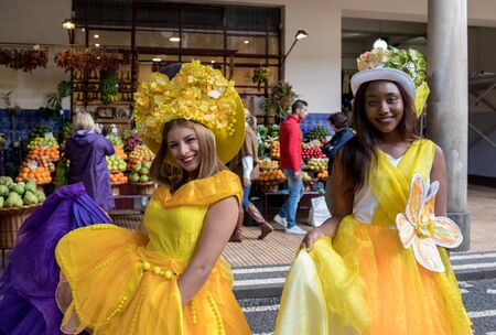 Funchal, Madeira, Portugal - April 23, 2018: Two beautiful girls in yellow dresses encourage shopping at Mercado dos Lavradores fruit and vegetable market in Funchal on Madeira Island. Portugal Publikacyjne