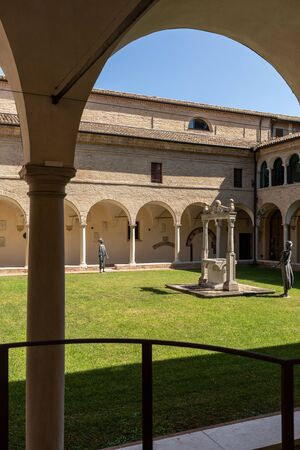 Ravenna, Italy - Sept 11, 2019: Courtyard with decorated columns, arches and green lawn of old Franciscan friars cloister near the Dantes Tomb and Basilica of San Francisco in Ravenna, Italy Publikacyjne