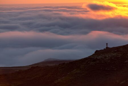 Silhouette of a man on the ridge above the sea of clouds, misty mountains at sunset in Iceland