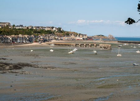 Boats on dry land at the beach at low tide in Cancale famous oysters production town, Brittany, France,