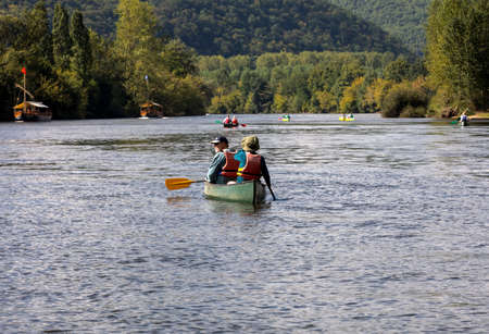 La Roque-Gageac, Dordogne, France - September 3, 2018: Canoeing and tourist boat, in French called gabare, on the river Dordogne at La Roque-Gageac, Aquitaine, France