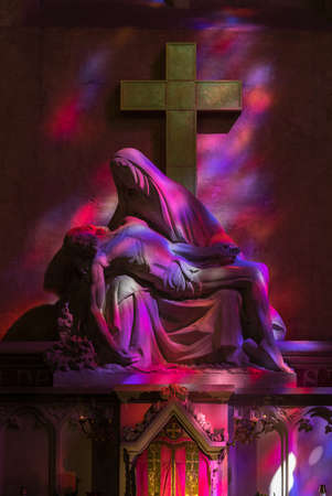 St Emilion, France - September 8, 2018: Pieta in Hues of Purple and red - symbolic reference to the color of the wine in the Collegiale church of St Emilion, France Editoriali