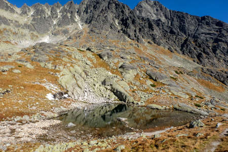 Pond in Valley of Five Spis Lakes surrounded by rocky summits, High Tatra Mountains, Slovakia.