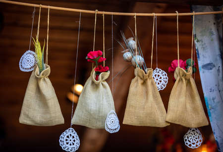 Linen pouches with medicinal herbs hanging in the window of the house Archivio Fotografico