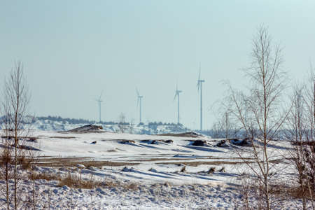 Open pit mine in winter with wind turbine system