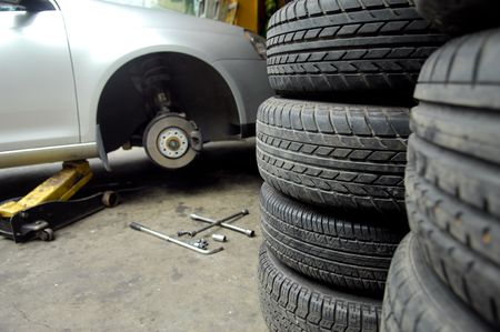 lugs: Mechanic tightening or loosening the lugs of an aluminum rim Stock Photo
