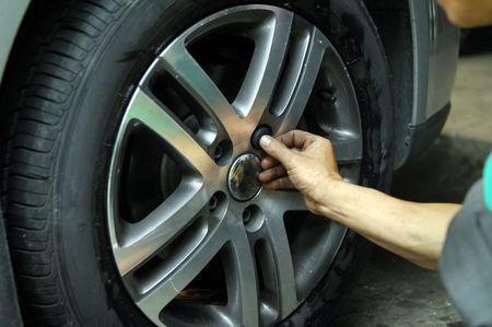 Mechanic tightening or loosening the lugs of an aluminum rim Stock Photo - 3708806