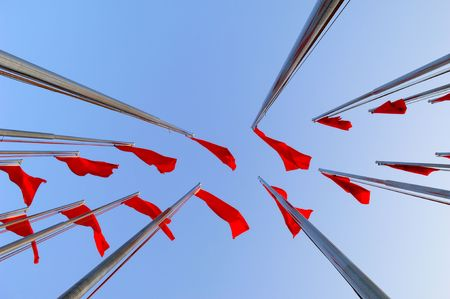 unfurl: red flags on blue sky background.  Stock Photo