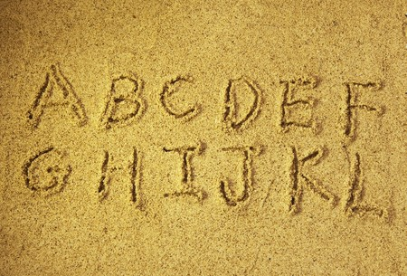 alphabet letters handwritten in sand on beach  photo