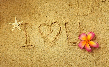 pink plumeria: i Love you in the sand Stock Photo