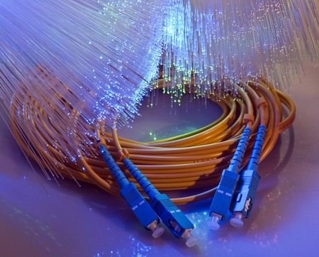 network connection plug: fiber cable closeup with fiber optical background  Stock Photo