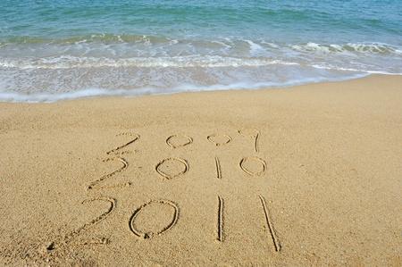 2011 year handwritten in sand on a beach   photo