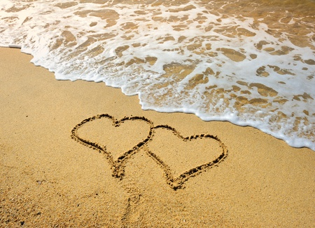 two hearts drawn in beach in sunset Stock Photo - 8627679
