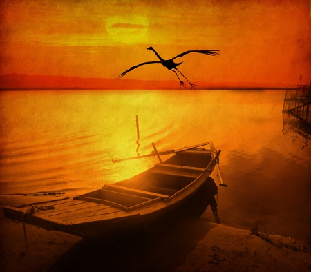 desolated: bird and old fish-boat on sandy beach with beautiful sunset on old grunge antique paper texture Stock Photo