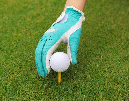 placing: gloved hand putting a golf ball on a tee  Stock Photo