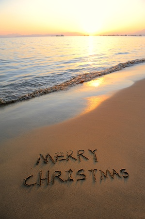 beach happy new year: Merry Christmas handwritten in sand on a beautiful beach  Stock Photo