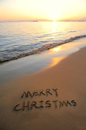 beach happy new year: Merry Christmas handwritten in sand on a beautiful beach  Stock Photo