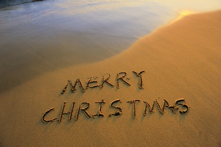 Merry Christmas handwritten in sand on a beautiful beach photo