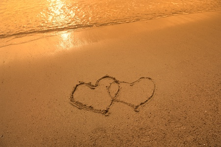two hearts drawn in beach in sunset Stock Photo - 11519434