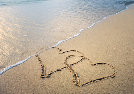 perdonar: dos corazones dibujados en la playa Foto de archivo