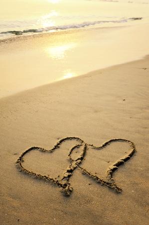 huellas de pies: dos corazones dibujados en la arena de una playa Foto de archivo