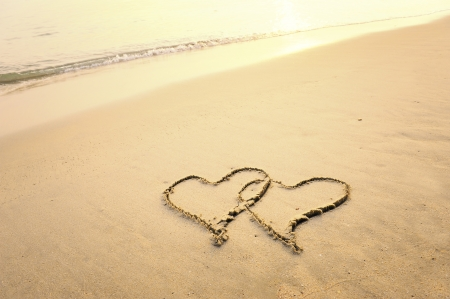 evoking: two hearts drawn on the sand of a beach  Stock Photo