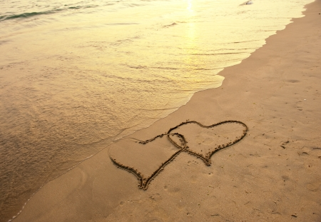 footprints in the sand: two hearts drawn on the sand of a beach  Stock Photo