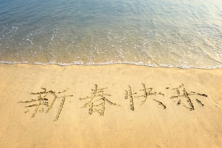 Chinese Calligraphy for happy new year written in the sand photo