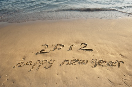 happy new year written in the sand  Stock Photo - 12120911