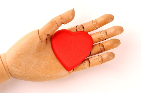 wooden mannequin s hands, holding red heart symbols photo