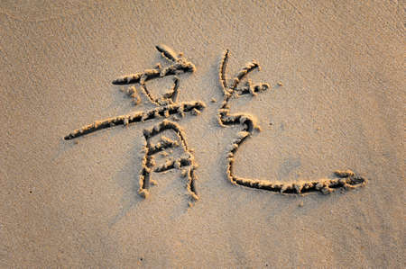 word mean dragon on tropical beach sand photo