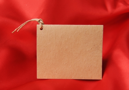 Blank tag tied with red silk satin background photo
