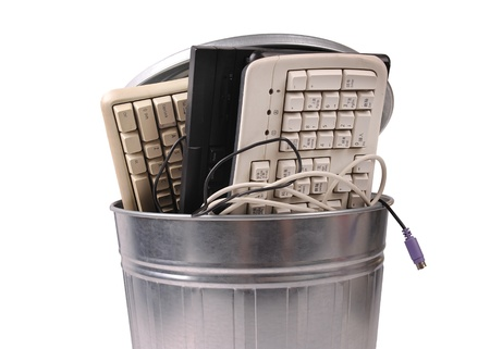 broken computer: different computer parts and phone in trash can Stock Photo