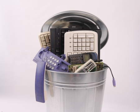 different computer parts and phone in trash can photo