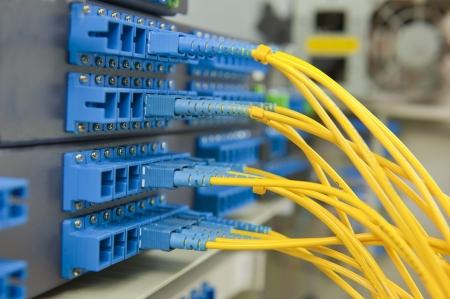 fibra óptica: Grupo de conmutador de fibra óptica de red con algunos cables de la red amarillas Foto de archivo
