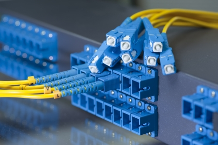 Panel of Fiber network switch with some yellow network cables photo