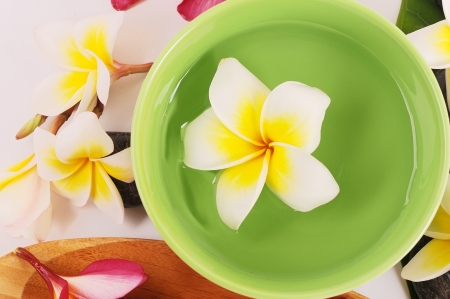 Frangipani and polished stone on bamboo mat photo