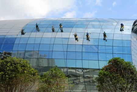 andamios: Los trabajadores industriales monta�ismo lavar ventanas de un edificio de gran altura
