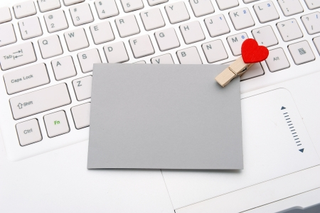 Laptop keyboard with small red hearts clothes pegs and sticky note photo