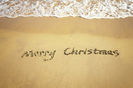 beach happy new year: Merry Christmas handwritten in sand on a beautiful beach