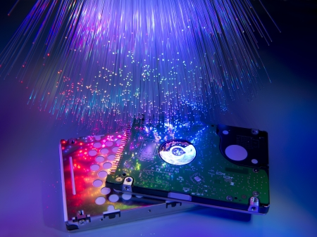 computer harddisk and heads on technology fiber optics background photo