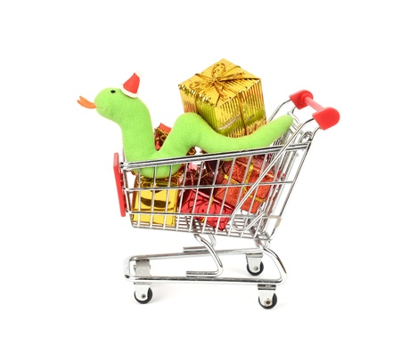 checkout line: Shopping cart fill with Christmas Decorations background and Cute Christmas snake Stock Photo